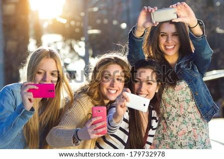 Outdoor portrait of group of friends taking photos with a smartphone in the street - stock photo