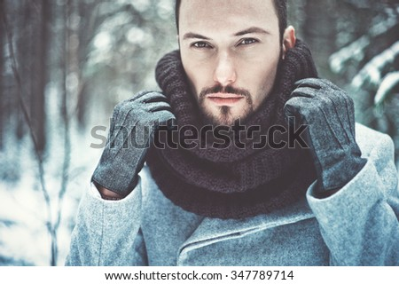 Outdoor portrait of handsome man in coat and scurf. Casual winter fashion - stock photo