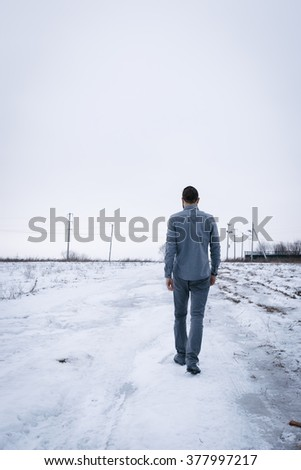 Outdoor portrait of handsome man in coat and scurf. Casual winter fashion