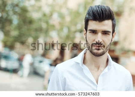 Outdoor portrait of handsome young man walking on the street, looking at camera.