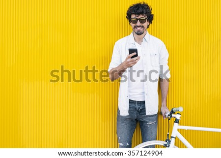 Outdoor portrait of handsome young man with mobile phone and fixed gear bicycle in the street. - stock photo