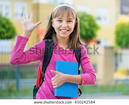 Outdoor portrait of happy child 10-11 year old with book and backpack. Girl stretching her right hand up for greeting. Back to school concept.
