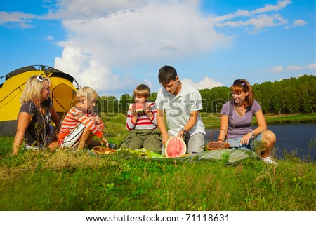 outdoor portrait of happy families at the picnic, young man is cutting watermelon - stock photo