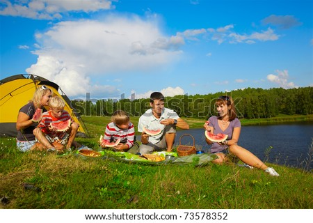 outdoor portrait of happy families enjoying watermelon at the picnic near camp tent
