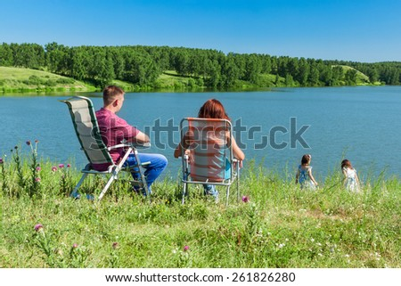 outdoor portrait of happy family near the lake - stock photo