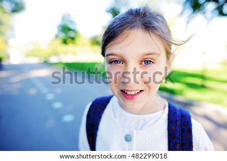 Outdoor portrait of happy girl 10-11 year old with backpack. Back to school concept.