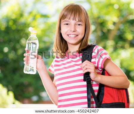 Outdoor portrait of happy girl 10-11 year old with schoolbag and bottle of fresh water. Back to school concept.