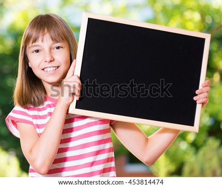Outdoor portrait of happy girl 10-11 year old with small blackboard. Back to school concept. - stock photo