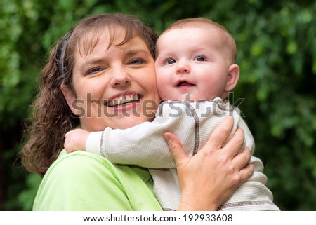 Outdoor portrait of happy mom with her baby son - stock photo
