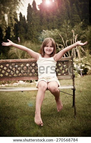 Outdoor portrait of happy smiling girl sitting on bench, legs and hands stretched - photo with lens flare - stock photo