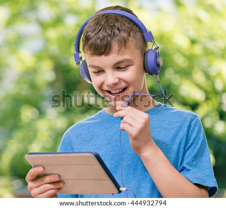 Outdoor portrait of happy teen boy 12-14 year old chating with family or friends using tablet - stock photo
