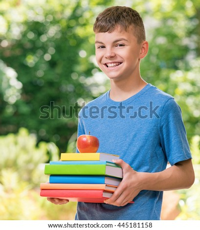 Outdoor portrait of happy teen boy 12-14 year old with books and apple. Back to school concept. - stock photo