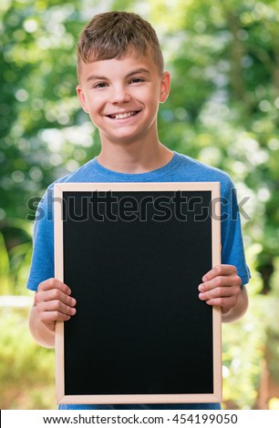 Outdoor portrait of happy teen boy 12-14 year old with small blackboard. Back to school concept. - stock photo