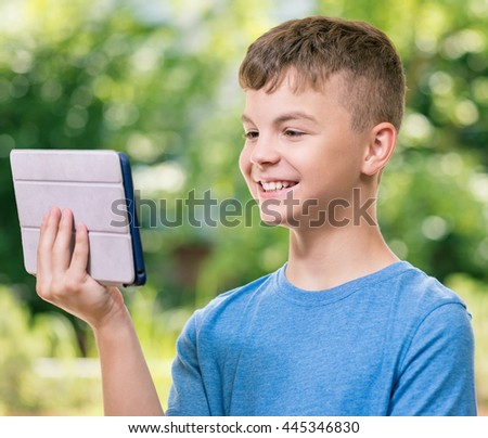 Outdoor portrait of happy teen boy 12-14 year old with tablet pc watching video in summer park - stock photo