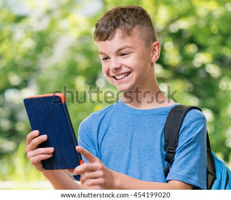 Outdoor portrait of happy teen boy 12-14 year old with tablet. Schoolboy watching media content in a tablet at park. - stock photo