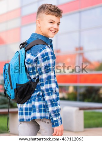Outdoor portrait of happy teen boy 12-14 years old with backpack. Young student beginning of class after vacation. Back to school concept.