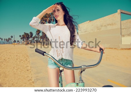 Outdoor portrait of happy woman biking in city park. Joy and happiness. - stock photo