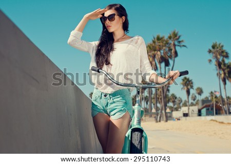 Outdoor portrait of happy woman biking in city park. Joy and happiness. Young woman in shorts, sunglasses on holidays. Venice, Los Angeles.