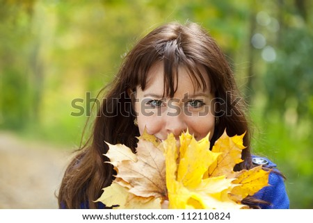 Outdoor portrait of happy woman in autumn with maple posy - stock photo
