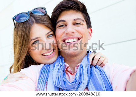 Outdoor portrait of happy young couple taking photos with a smartphone in the street. Selfie concept  - stock photo