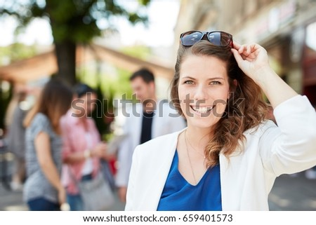 Outdoor portrait of happy young woman smiling, looking at camera.