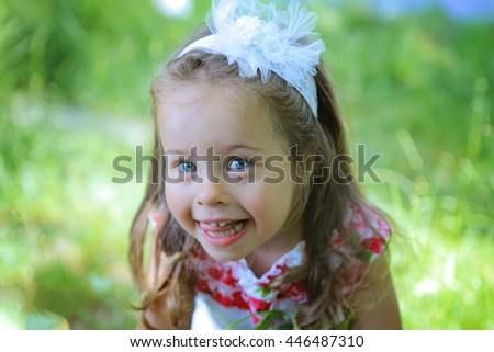 Outdoor Portrait of joyful cute smiling little 4-years girl with long hair. Happy five years beautiful kid laughing in the garden looking at camera headshot close-up - stock photo