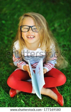 Outdoor portrait of laughing sweet little girl in a park - stock photo