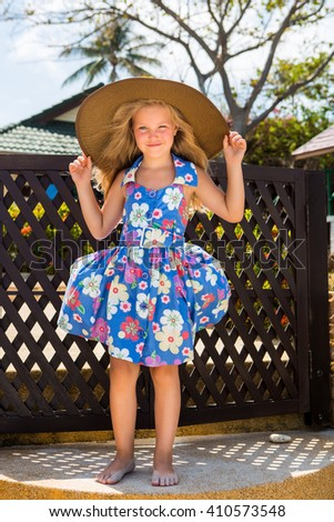 Outdoor portrait of little cute girl in blue floral dress and beach straw hat. She holds her big hat and smile. Summer sunny day. House with wooden fence at tropical background. Mothers day. - stock photo