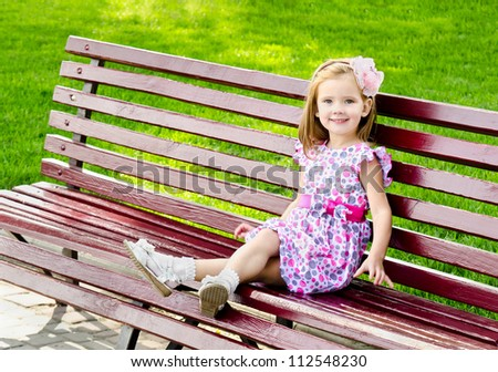 Outdoor portrait of little girl sitting on a bench in park - stock photo