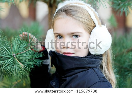 Outdoor portrait of little girl wearing white earmuffs - stock photo