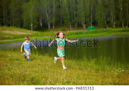 outdoor portrait of little kids running with butterfly net along the bank of the pond