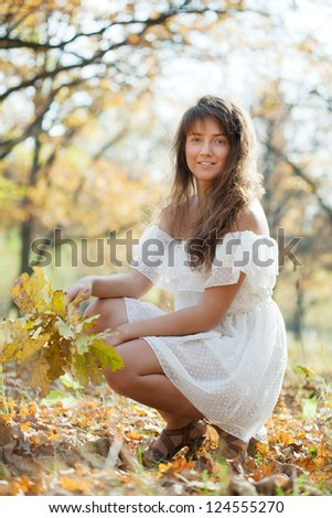 Outdoor portrait of long-haired girl with oak posy in autumn