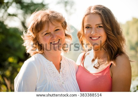 Outdoor portrait of mature mother with her teenage daughter - backlit with sun - stock photo
