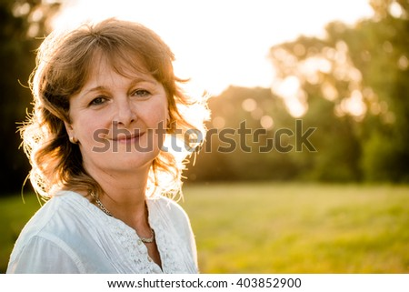 Outdoor portrait of mature woman - in nature at sunset - stock photo