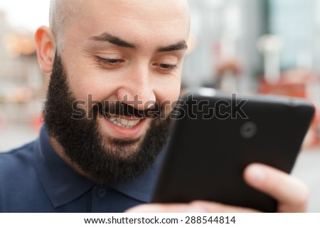 Outdoor portrait of modern bearded man with tablet in the street