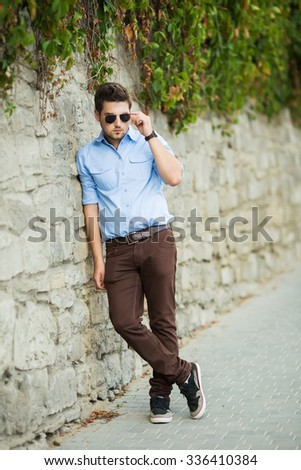Outdoor portrait of modern young man watch on time in the street.