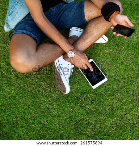 Outdoor portrait of modern young man with mobile phone, tablet on the grass. - stock photo