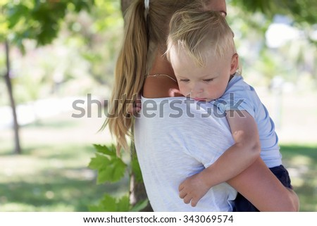 Outdoor portrait of mother and sad crying son in a summer park - stock photo