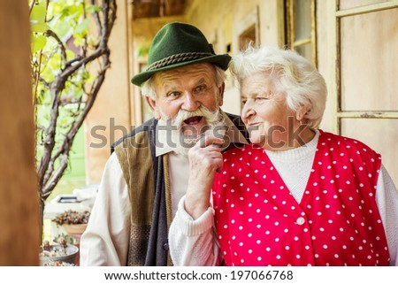 Outdoor portrait of old couple standing by their village house - stock photo