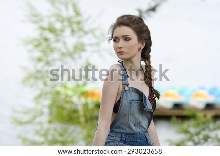 outdoor portrait of pretty girl with summer casual look and braid hair-style. Posing with lake water on background with bikini under denim overalls  - stock photo