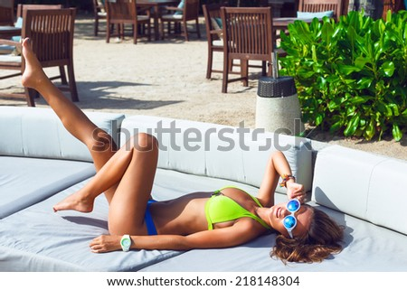 Outdoor portrait of pretty slim tanned woman, having fun alone, relaxed on big white sofa at luxury resort on hot tropical counter, wearing stylish neon bikini and sunglasses, put her leg in the air. - stock photo