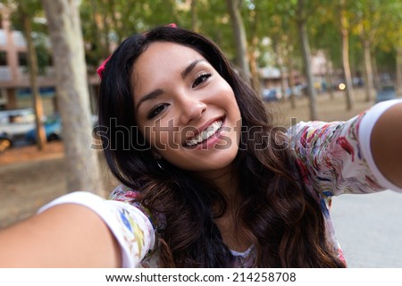 Outdoor portrait of pretty student girl taking a selfie. - stock photo