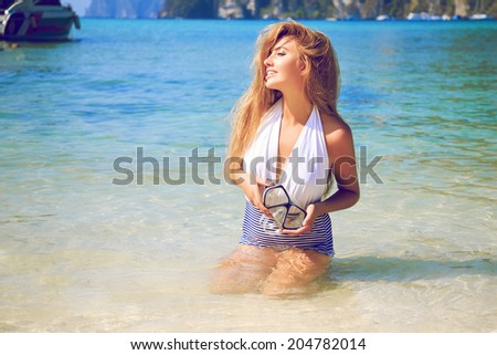 Outdoor portrait of pretty tan sportive woman getting sunbathe at topical island with clear blue water, Thailand Koh Phi Phi. - stock photo