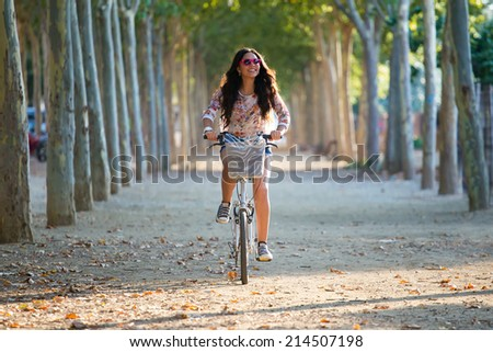 Outdoor portrait of pretty young girl riding bike in a forest. - stock photo