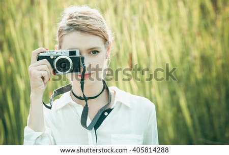 Outdoor portrait of pretty young girl with retro vintage camera - stock photo