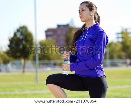 Outdoor portrait of pretty young woman drinking water after running. - stock photo