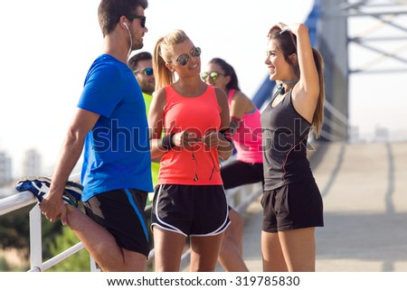 Outdoor portrait of running people doing stretching in the park. - stock photo