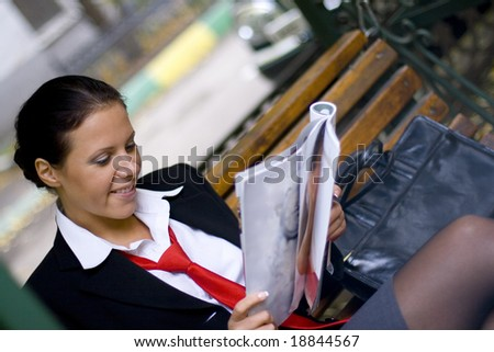 outdoor portrait of smiling businesswoman reading magazine - stock photo