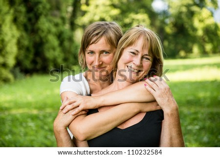 Outdoor portrait of smiling happy senior mother with her adult daughter - stock photo