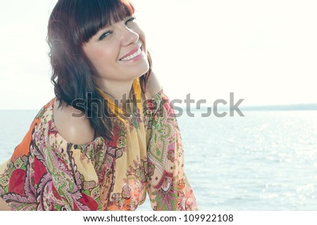 Outdoor portrait of smiling young woman enjoying summer time - stock photo